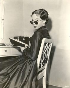 Leslie Caron reading in her dressing room during the filming of The Man with a Cloak, 1951.