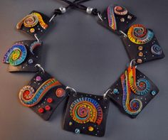 Polymer Clay Necklace, the contrast between the black tiles and the rainbow colored spirals is fascinating and eye catcing...