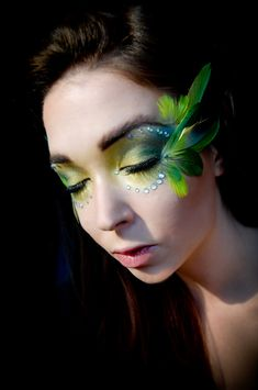Vibrant parrot inspired make-up with feathers and crystals.