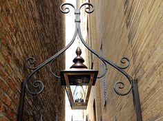 Partnered with Craig Bergmann Landscape Architects to fabricate a hand-forged iron arch and hanging Bevolo London Street lantern, portraying the setting's historic aesthetic.