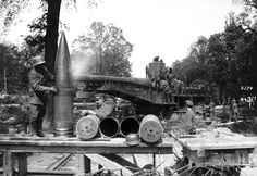 """A German soldier rubs down massive shells for the 38 cm SK L/45, or """"Langer Max"""" rapid firing railroad gun, ca. 1918. The Langer Max was originally designed as a battleship weapon, later mounted to armored rail cars, one of many types of railroad artillery used by both sides during the war. The Langer Max could fire a 750 kg (1,650 lb) high explosive projectile up to 34,200 m (37,400 yd). (National Archive/Official German Photograph of WWI)"""