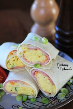Eggs Wraps   2 eggs 2 small flour tortillas, 8″ 1 green onion, chopped 4 thinly sliced pieces of ham Salt and pepper ¼ cup Tex Mex cheese, grated