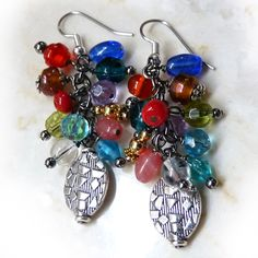 Super colorful fun earrings!  Each beaded earring has 12 handmade dangles, each with a different crystal, lamp worked glass or metal bead. The metal finishes are a combination of stainless steel, gold, antique pewter and gunmetal. Lots of movement, very artsy. #gift #handmade Part of the under $50 collection.