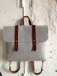 this a very lightweight, durable, industrial felt and vegetable tanned leather rucksack  made to convert from a backpack to a crossbody bag by