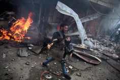 A Syrian man carries the body of a child, killed in an air strike by government forces in Douma, Syria.