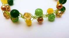 This amazing bracelet was knitted with light green tone silver plated wire and decorated with the beads of natural Yellow Topaz, Green Agate, glass beads and crystals.