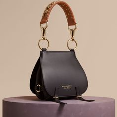 An equestrian-inspired runway satchel in smooth bridle and grainy leathers from Burberry. Reflecting traditional British saddlery, the soft practical shape is crafted with utilitarian clasps, a grooved border and burnished edges.