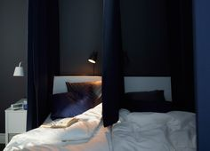 A dark blue padded curtain placed between the pillows of a double bed means you…