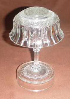 A medium sized glass mushroom made from a wine glass and small glass bowl. I have glued a glass plate to the base of the wine glass for stability, to prevent it toppling over in the garden. The plate can be covered with soil or leaf-litter and hidden from view. See the next photo for an example of the 'invisible base plate' covered by leaf-litter. Tags: Glass Mushroom, Repurpose, upcycling glass dishes, garden junk, vintage dishes, op-shop, Made By Mim