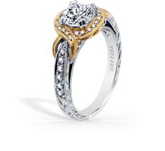 This elegant design is a halo engagement ring from the Pirouetta collection. It features 0.23 ctw of diamonds. The signature handcrafted details include wheat hand engravings, signature filigree, peek-a-boo diamonds, milgrain edging and yellow gold accents. The center 1 carat round stone (shown) is a customized option.