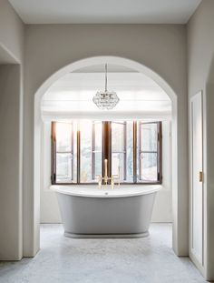 A striking archway makes the oversized tub a focal point in this bathroom.