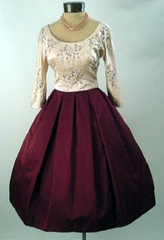 1950's evening dress, in lustrous deep maroon silk satin and pale peach. Features a scooped neckline, three-quarter length sleeves, darted and seamed bodice with stunning embroidered floral designs embellished with sequins and beading, piped waistline, and a full skirt with box pleats at waist.  Sold at Stix, Baer and Fuller.
