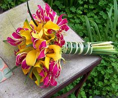 Curling petals of pink-and-yellow gloriosa lilies soften the minimalist appearance of the bold yellow calla lilies. Two very sturdy flowers, calla lilies & gloriosa lilies