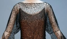 """VIONNET BLACK LACE EVENING DRESS, 1930's. Black boatneck having long sleeve flaring into open bell at elbow, full skirt pieced in a pattern of lace diamonds and tulle, under-dress in sheer black over pale pink silk, side hook & eye closures. Labeled """"Madeleine Vionnet Depose"""" with thumbprint. Detaile front"""