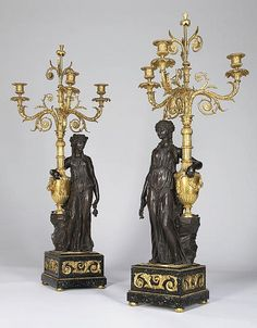 A PAIR OF FRENCH PATINATED-BRONZE AND ORMOLU THREE-LIGHT CANDELABRA <br />19TH CENTURY <br />Of Louis XVI style, each with acanthus and floral-cast scrolling branches issuing from a garland-draped urn being held by a draped female figure standing on a square porphyry base with scrolling acanthus-cast mounts (2)<br />