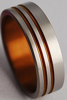 I like this, maybe not with orange for him though... titanium mens wedding band with orange inlay