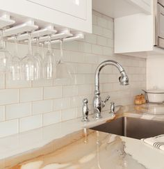 white glass subway tile as backsplash, stemware holders on the underside of the cabinet