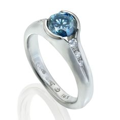 Etienne Perret Danielle engagement ring featuring a split-bezel-set blue color enhanced natural diamond accentuated by gvs diamonds in 18kt white gold
