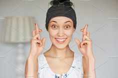 Close up portrait of young happy superstitious woman looking at the camera crossing her fingers for good luck. Student girl hoping her dreams come true. Human face expressions, emotions, feelings by WAYHOME studio on @creativemarket