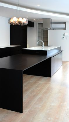 Black and white contemporary kitchen. Love the color of the flooring and lighting