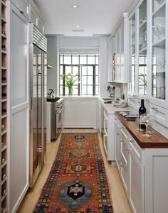 An antique runner fits the floor just so and brings in elegance and refinement to a tight space. And notice the shallow counter depths.