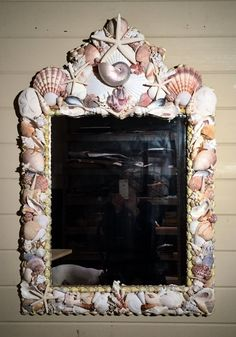 This wooden frame has a lovely pediment to showcase large shell arrangements. Nautilus shells, starfish, scallop shells, cone shells and many more are beautifully arranged on the front and sides of the mirror. It measures approximately 42 x 28 x 4.