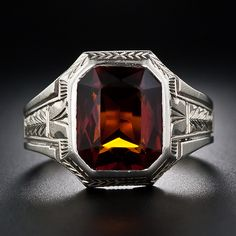 This sleek and sophisticated 1930s vintage gent's ring centers on a deep amber color Madeira Citrine. The dusky gemstone resides in a superbly sculpted white gold mounting adorned with consummate geometric Art Deco and neo-classical design motifs. Sharp.