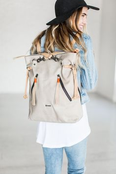 Easily convertible backpack and tote with the detachable backpack straps and side compression straps. Features include three external zipper pockets with a genuine leather tassel as the zipper puller.