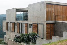 Os dois pórticos de concreto aparente são interligados por um corpo longitudinal em nível inferior, onde situam-se os dormitórios. A Casa Ithayê foi projetada por Apiacás Arquitetos