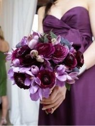 The bridesmaids will carry clutch bouquets of lavender spray roses, dark purple ranunculus, wine anemones, and fig colored cymbidium orchids wrapped in pale gold ribbon.