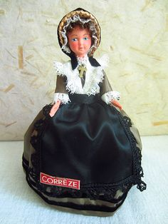 Cute little doll representing the department of Corrèze in the Limousin Region of France. She wears a straw hat on her head, trimmed with a black