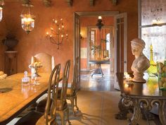 The dining room glimmers with light reflected in a mirrored screen propped in the corner of the room. The eighteenth century Portuguese side table, decorative bust and faux paint lend a Mediterranean vibe to the space.