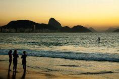 Banhistas observam praticante de stand up paddle. Foto: Fernando Quevedo / Agência O Globo