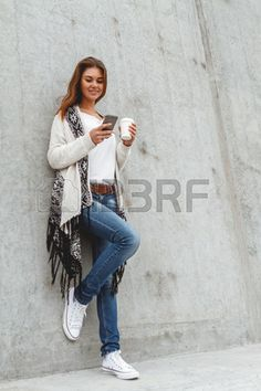 Portrait of a young beautiful girl with a phone hands and coffee in the warmth of a knitted sweater in a concrete wall