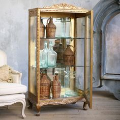 A treasure trove of unique antiques, the classic French and European style pieces boast an original patina that's been aged and distressed from years of love and everyday use. With its glass shelves, mirror back and exquisite floral carving, this Louis XV-style vintage vitrine displays your treasures in pure elegance. A distressed gilt finish completes the elegant cabinet's aesthetic. Circa 1940.