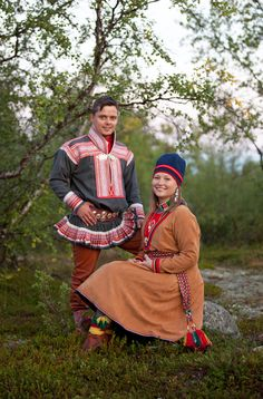 The man is wearing a kirtle from Kautokeino, Norway and the woman a Lule Sami kirtle from Sweden. Her kirtle is of chamois leather and he has chosen to have the rather unusual combination of grey broadcloth with the ribbons stitched on to white panels. The traditional colors would be blue with red panels.