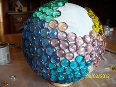 This is my bowling ball yard art before it was completed.  I filled the holes with kitchen caulking & then when dry, painted with a good paint.  Then started putting the beads on in a random pattern using a really strong craft glue.