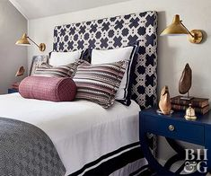 Keep proportion and room size in mind when choosing a headboard. A room with tall ceilings can handle a tall headboard, while a room with slanted ceilings makes an average-sized headboard look larger that normal. As seen here, this navy-and-white upholstered headboard adds scale to a small double bed. However, a too-tall headboard would dwarf the rest of the room or even run into the ceiling. Wall-mounted light fixtures flank the sides of the bed, matching the headboard height for a…
