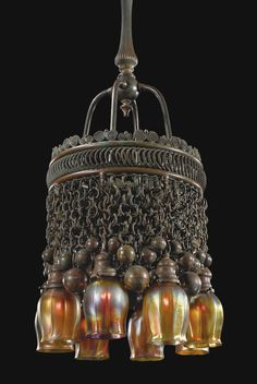 American designed at Tiffany Studio - NY, A Moorish eight-light chandelier, created with patinated bronze, and favrile glass shades.