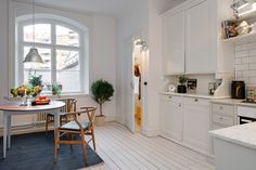 Zdjęcie: szary dywan i drewniany stół w białej kuchni