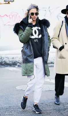 Cara Delevingne in her signature sporty look, which includes a comfortable sweatshirt, athletic pants, sneakers, and a parka