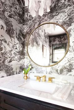 Beautiful powder room bathroom decor, with an elegant wall mirror by Martyn Lawrence Bullard and black and white wallpaper.