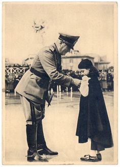 Mussolini giving a medal to a young little girl
