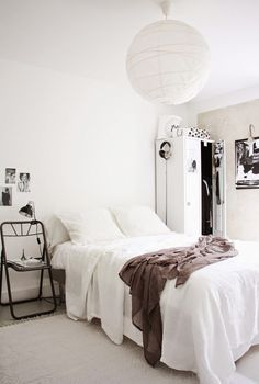 Swedish bedroom with a white paper lantern over the bed and a locker doubling as a wardrobe