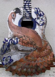 Birds decoration on musical instruments: Peacock guitar with painted blue and white flowers: Beautifully carved wood with coloring - https://www.pinterest.com/claxtonw/4-5-6-strings/  4 5 6 Strings #Pinterest board.  A MOST POPULAR RE-PIN, https://www.pinterest.com/DianaDeeOsborne/ddo-most-popular-re-pins/ - Notice the intricate carvings of individual wooden feathers. Photo source: Saber Pacific