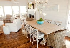 Suzie: Munger Interiors - Chic beachy dining room space with white paneled walls, reclaimed  table