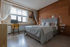 Contemporary bedroom with wooden accent headboard wall
