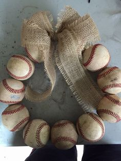 "Baseball wreath with either an ""L"" in middle or a chalkboard sign   Process: drill hole in balls. Put on wire hanger. Hook ends together. Make burlap bow. Tie bow on with twine."