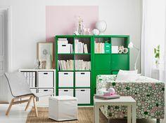 Obývacia izba s zelenými a bielymi policovými dielmi so škatuľami a knihami. Na obrázku v kombinácii s dvojmiestnou pohovkou s ružovo-zeleným bavlneným poťahom a bielym príručným stolíkom.