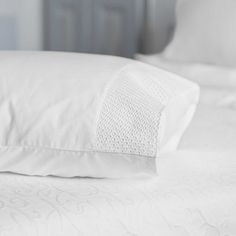 Pearl's crisp, white pillowcases are finished with  detailing and embroidery along one side.